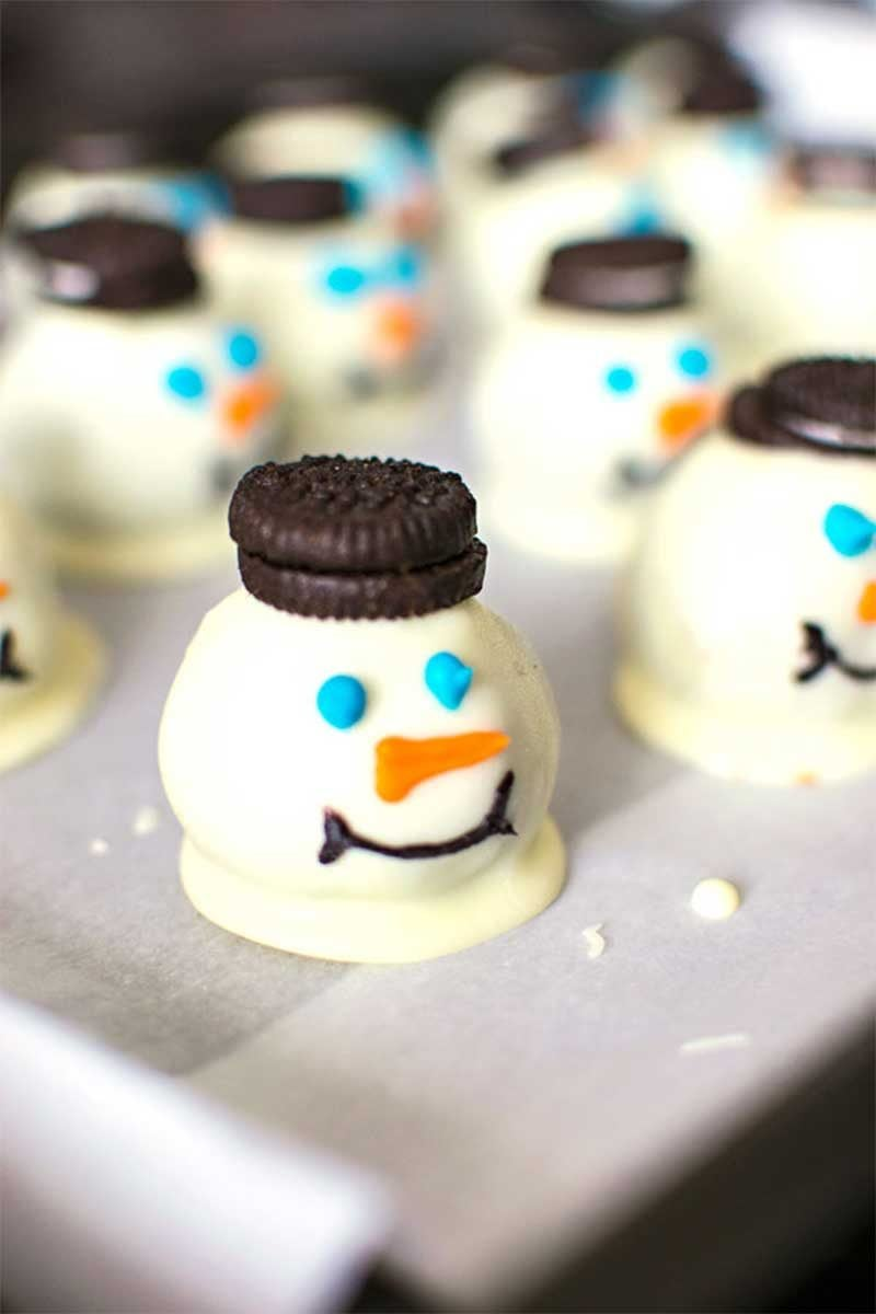 Melting Snowmen Cookie Balls! Festive snowmen cookies made with a crushed Oreo mixture that's dipped in white candy and topped with Mini Oreo hats. VERY easy to make! | HomemadeHooplah.com
