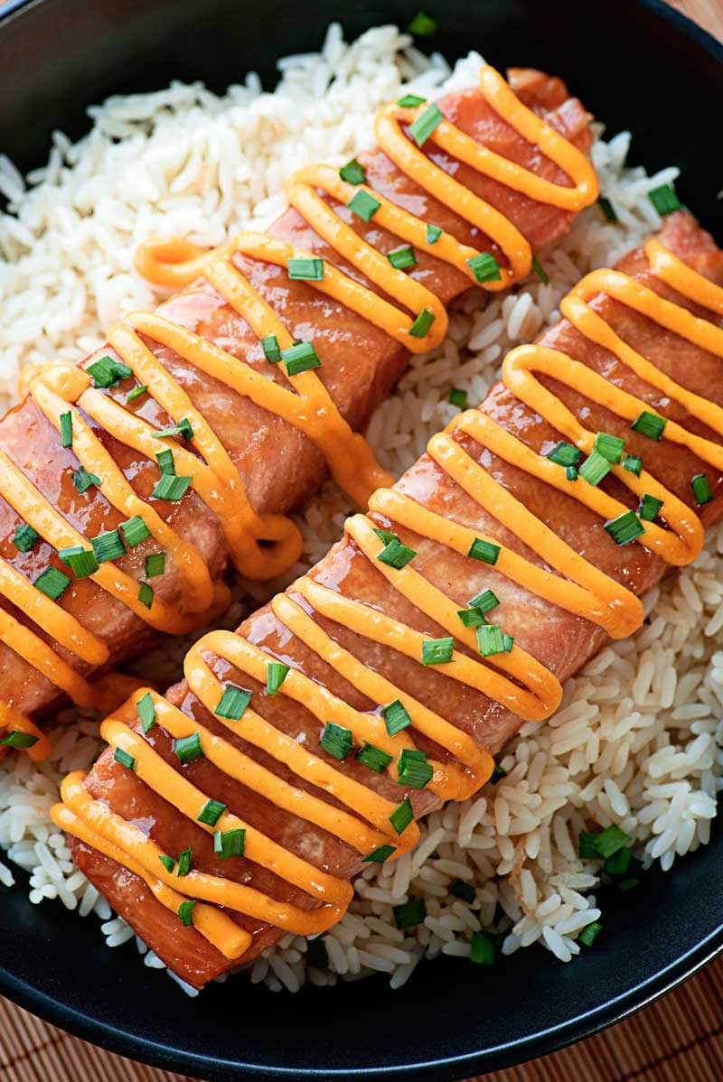Fresh salmon marinated and baked in a homemade teriyaki sauce and topped with a sriracha cream sauce - make it as sweet or as spicy as you like! | HomemadeHooplah.com