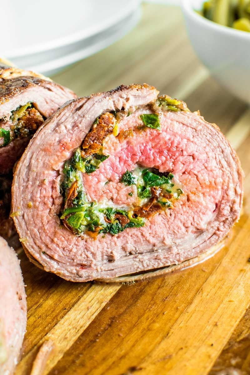 Baked Stuffed Flank Steak! Spice up your boring steak dinner by filling a fine cut of meat with spinach, mozzarella, and sun-dried tomatoes. It's easy to tailor to your tastes, too! | HomemadeHooplah.com