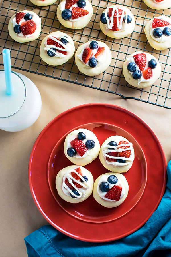 Patriotic Fruit Pie Cookies! Celebrate Independence Day with delicious fruit pie cookies - a soft butter cookie topped with cream cheese frosting, chopped strawberries, and blueberries. | HomemadeHooplah.com