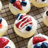 Patriotic Fruit Pizza Cookies! Celebrate the patriotic holidays & events with these festive soft butter cookies topped with cream cheese frosting, chopped strawberries, and blueberries.   HomemadeHooplah.com