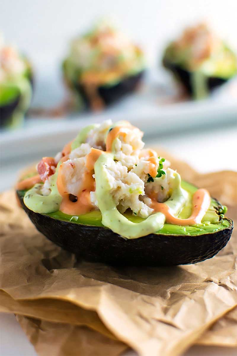 Seafood Stuffed Avocados! Halved avocados filled with chopped shrimp, fresh crab, and tomato and then drizzled with sriracha and avocado creams on top.   HomemadeHooplah.com