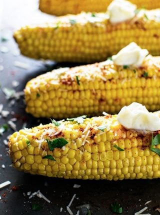 Baked Smoky Parmesan Corn! Baked corn on the cob with garlic butter, smoked paprika, parmesan, and a sprinkling of parsley. | HomemadeHooplah.com