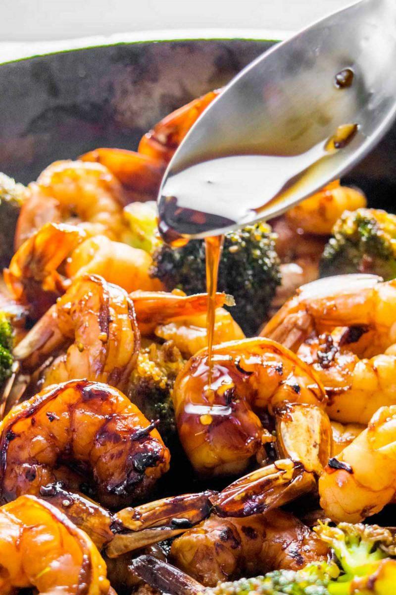 Drizzling honey garlic sauce on shrimp with broccoli.