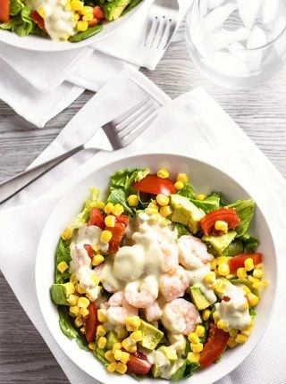 Shrimp Salad with Creamy Pesto Dressing! Butter garlic shrimp on a bed of crisp lettuce with avocado, tomato, and corn and a creamy pesto dressing drizzled on top. | HomemadeHooplah.com