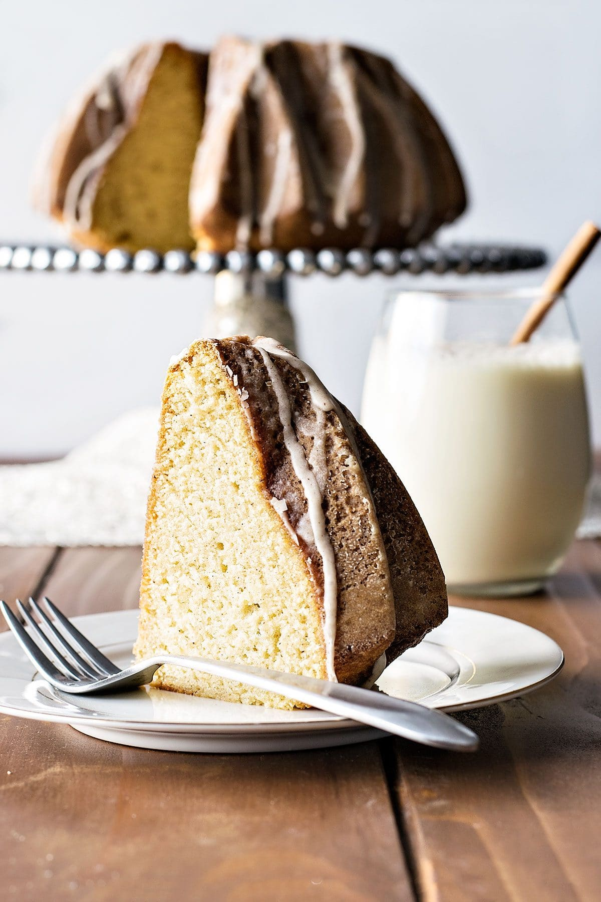Ultra moist and buttery bunt cake flavored with eggnog, rum, cinnamon, and nutmeg, then covered with a sweet eggnog glaze. It's a sweeter way to enjoy the holiday season's favorite drink! | HomemadeHooplah.com