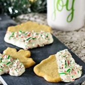 Peppermint Crunch Sugar Cookies! Festive sugar cookies with a twist: dipped in white chocolate and sprinkled with crushed candy canes. And they're only 4 ingredients to make! #NestleTollHouse #BakeSomeonesDay #HolidayRemix #ad   HomemadeHooplah.com
