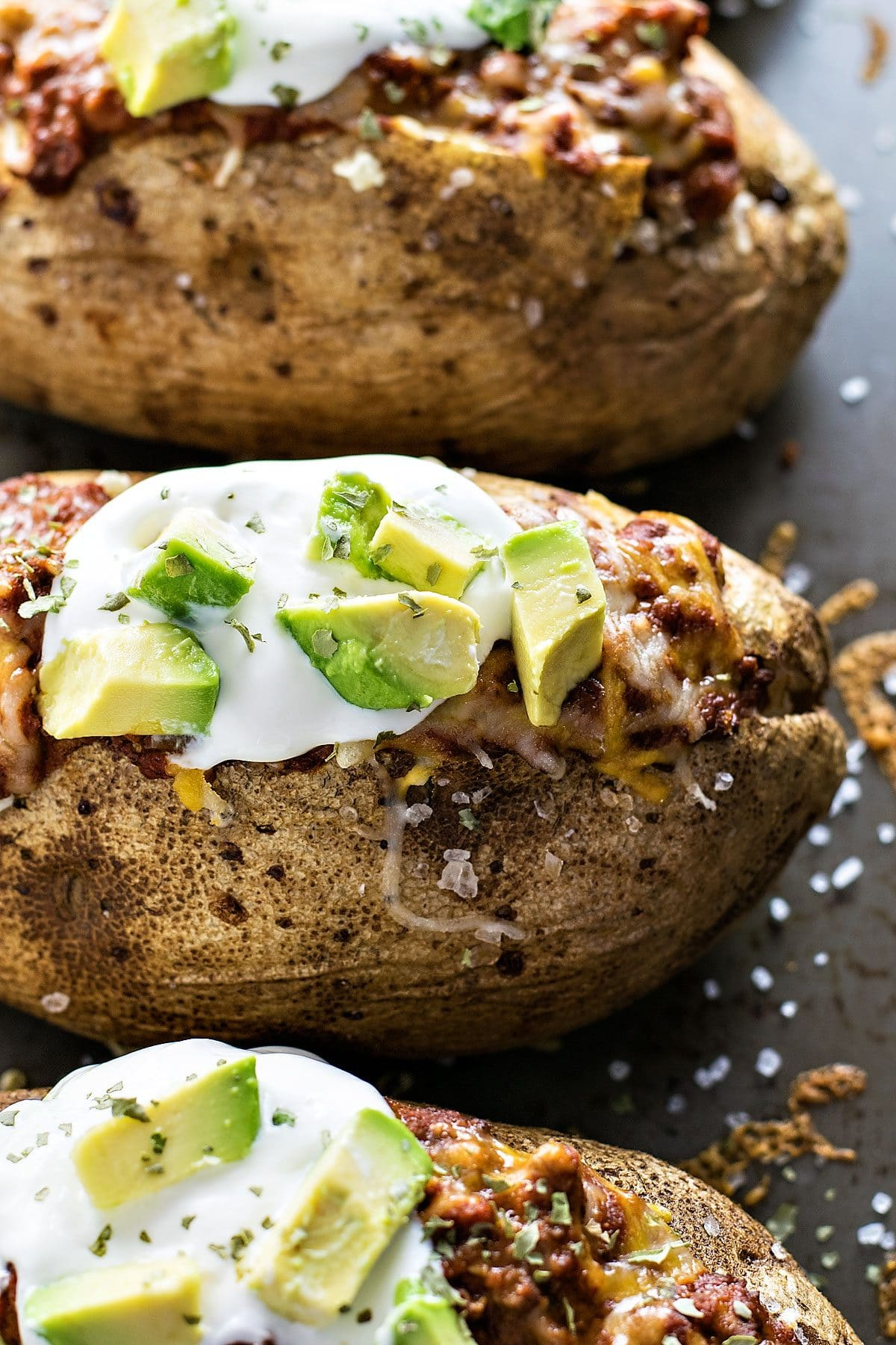 Chili Stuffed Potatoes! Chili baked potatoes filled with Hormel Chili and Mexican cheese then topped with sour cream, avocado, and cilantro. Easy to make and a perfect for a party! #spon #HormelChiliNation | HomemadeHooplah.com