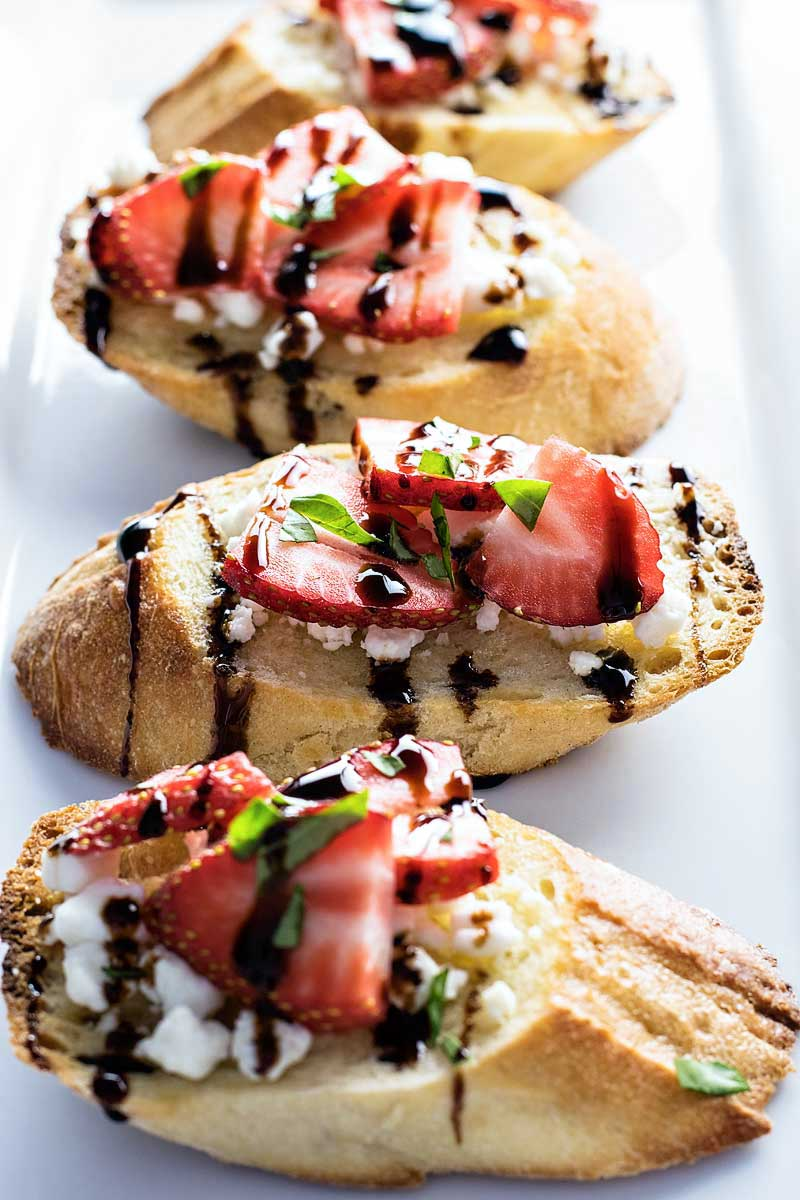 Strawberry and Goat Cheese Bruschetta! Get ready for summer with this festive appetizer! Sweet strawberries, tart balsamic, flavorful basil, and tangy goat cheese, all on a comforting baguette.   HomemadeHooplah.com