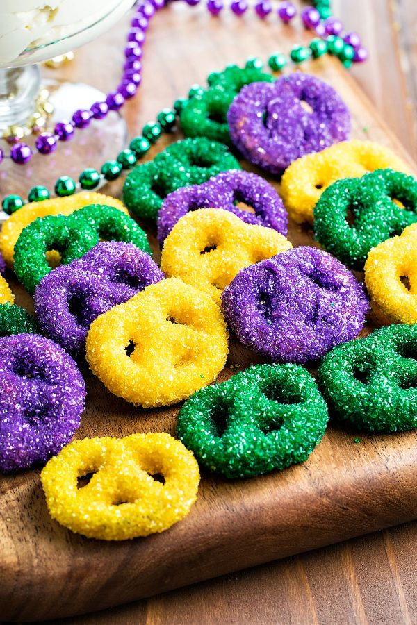 King Cake Dip! Enjoy this Mardi Gras favorite the easy way: cake batter dip topped with caramel and pecans, then served with candy and sprinkle dipped pretzels.   HomemadeHooplah.com