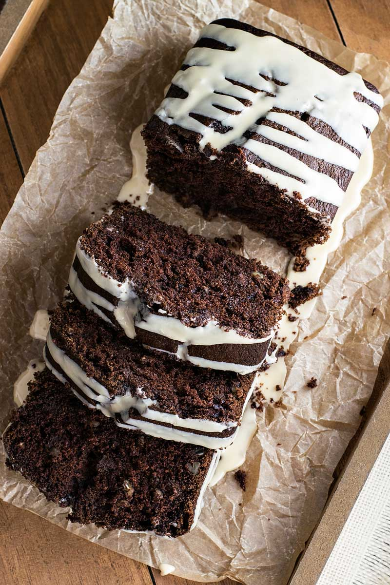 Baileys Dark Chocolate Guinness Bread! Rich, dark chocolate Guinness bread laced with chocolate chips and walnuts and then frosted with a sweet Baileys glaze. It's the perfectly indulgent bread! | HomemadeHooplah.com
