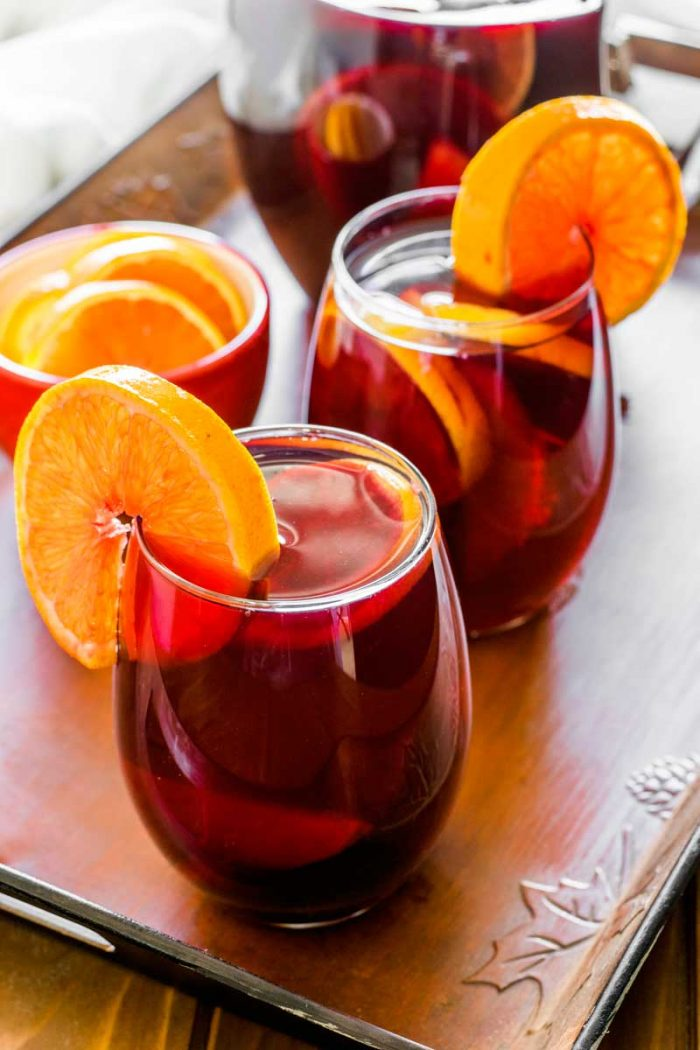 Orange Mango Sangria! Delicious orange mango sangria with sweet red wine infused with mango, orange, lemon, and lime, then spiked with a surprise shot of orange cointreau.   HomemadeHooplah.com