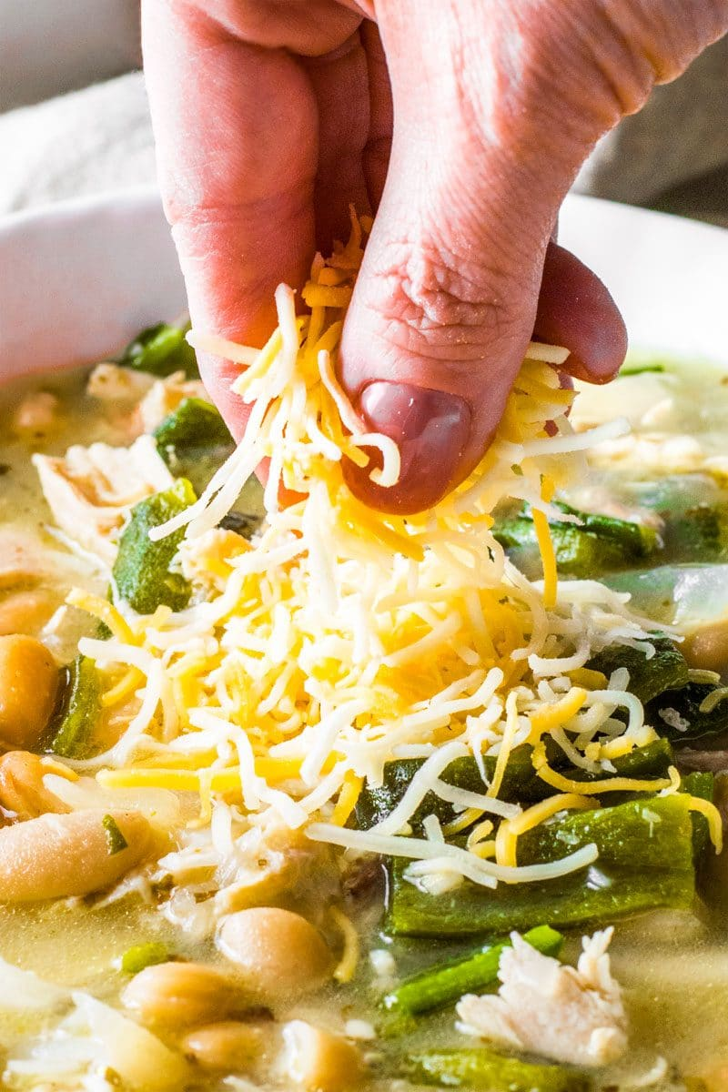 White Chicken Chili! A white chicken chili recipe made with whole chicken, homemade chicken broth, tender poblano chiles, and flavorful cannellini beans. This chilly weather comfort food will quickly become a new dinner favorite! | HomemadeHooplah.com