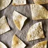 Homemade Baked Tortilla Chips! These baked tortilla chips are easy to make and SO much better for you than fried chips. Plus you make your own unique and interesting flavors!   HomemadeHooplah.com