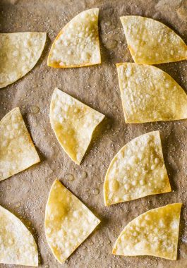 Oven Baked Tortilla Chips! Whether you're craving a snack or need something to serve with a party dip, these oven baked tortilla chips are easy to make and SO much better for you than fried chips. Plus, you can use your own seasonings to create unique and interesting flavors! | HomemadeHooplah.com