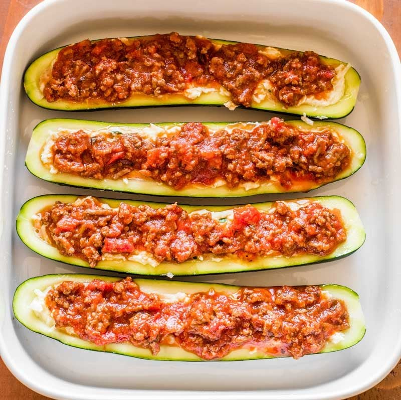 Before baking, drizzle the meat and sauce mixture on top of the zucchini boats.