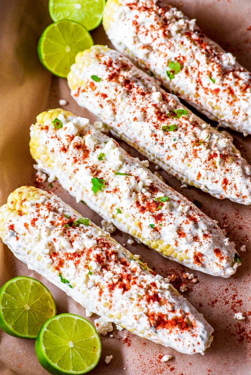 Baked Mexican Corn! Classic Mexican corn on the cob that's flavored with feta cheese and smoked paprika and makes for a perfect appetizer, side dish, or simple dinner. Plus, this Mexican street corn is baked, so it's easy to whip up this summer favorite all year long! | HomemadeHooplah.com