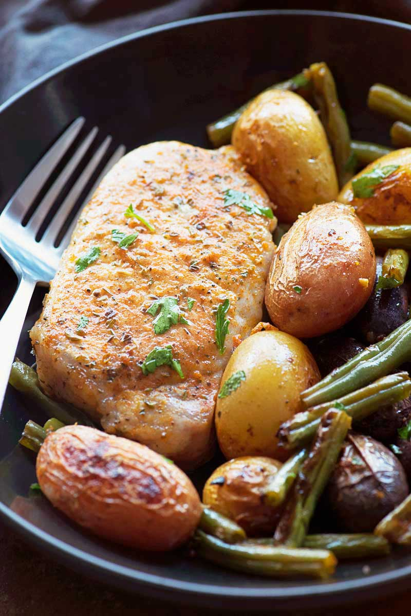 One Pan Smoky Ranch Pork Chops with Veggies! Savory ranch pork chops with a touch of smoked paprika baked on one baking sheet with assorted baby potatoes and green beans. | HomemadeHooplah.com