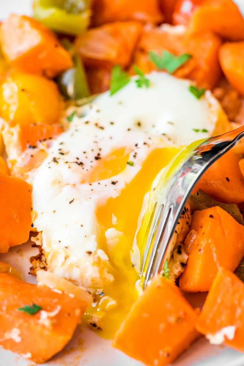 Sweet Potato Hash with Fried Eggs! Tender and delicious sweet potato cooked with onion, bell peppers, grape tomatoes, and a couple of fried eggs cooked in the middle. | HomemadeHooplah.com