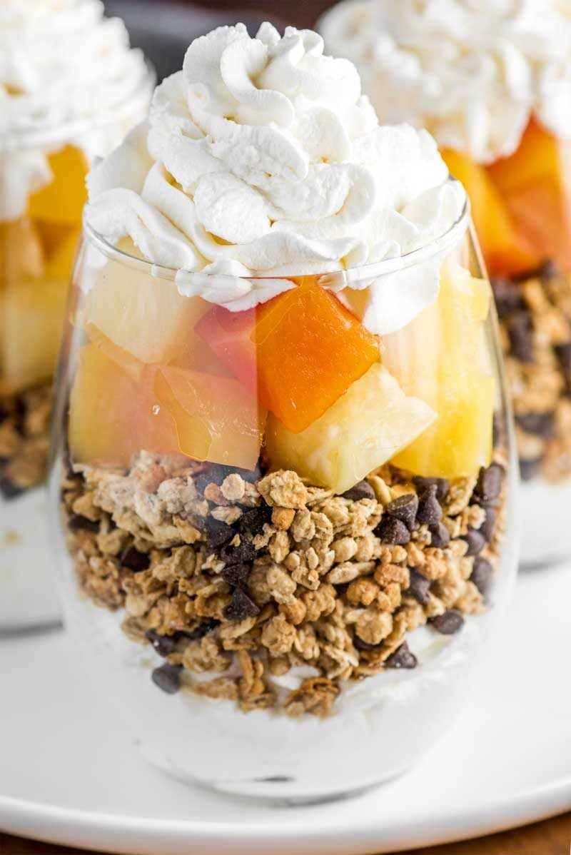 Tropical Fruit Parfaits! Decadent parfaits made with homemade whipped cream, granola, mini chocolate chips, and a tropical blend of fruit that comes together in just 15 minutes! FruitOnDemand AD @DoleSunshine | HomemadeHooplah.com
