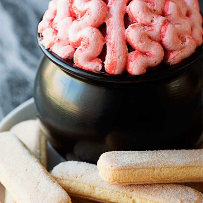 Brain Dip! This creepy brain dip is as tasty as it is fun! Red velvet cake batter dip is covered in cream cheese frosting and served with ladyfingers for dipping. | HomemadeHooplah.com
