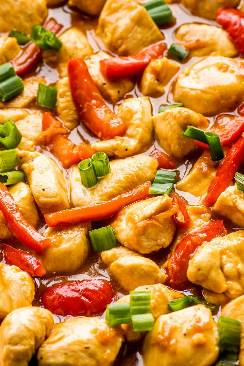 Orange Szechuan Chicken! Savory bites of chicken and tender bell peppers are cooked in an orange-ginger sauce in this delicious & flavorful dinner. It makes great leftovers, too! | HomemadeHooplah.com