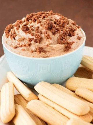 Churro Cheesecake Dip! The best way to enjoy a sugary cinnamon churro! Creamy cheesecake laced with cinnamon cream that's topped with a cinnamon crumble and served with cookies. | HomemadeHooplah.com