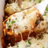 Sausage & Spinach Stuffed Shells! Jumbo pasta shells stuffed with a mix of ricotta, mozzarella, and spinach that's topped with crumbled sausage and cheese and baked on a bed of pasta sauce. #sponsored #SimmeredinTradition #Ragu | HomemadeHooplah.com