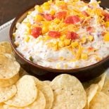 Fiesta Ranch Dip! No party is complete without this delicious homemade ranch dip! Smooth sour cream mixed with cheddar cheese and zesty tomato, green chili, and corn. #ad @shamrockfarms | HomemadeHooplah.com
