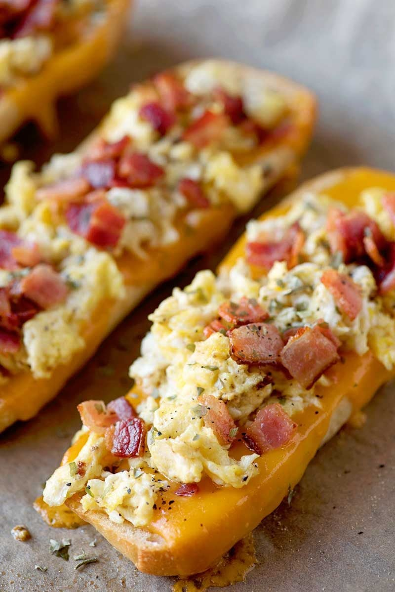 #ad Bacon, Egg, and Cheese Breakfast Boats! Toasted french bread covered fluffy egg, crispy bacon, and melted Sargento cheese make for a quick and easy breakfast solution for any day of the week! #RealCheesePeople | HomemadeHooplah.com