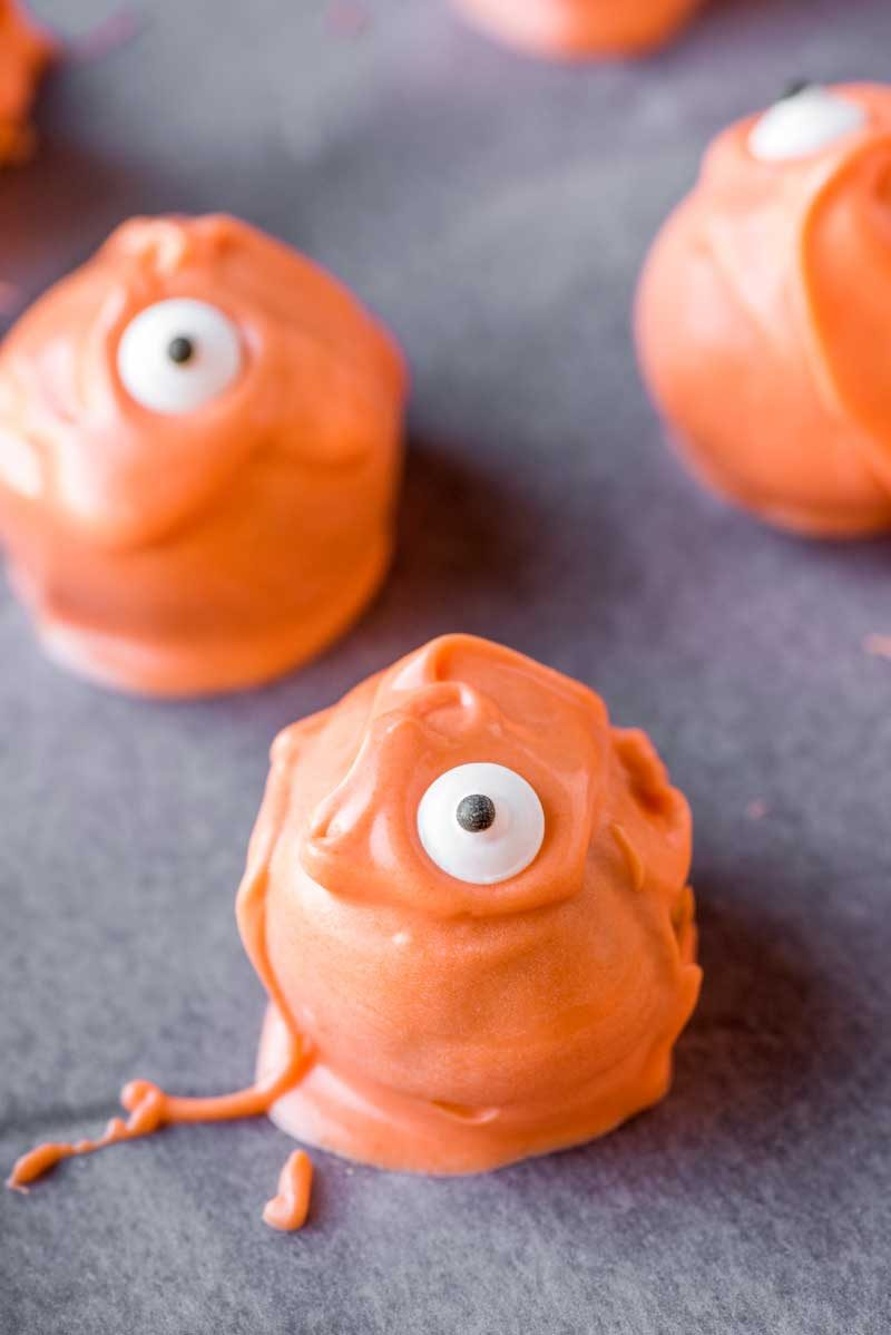Monster Halloween Truffles! These adorable Halloween truffles are filled with sweet pumpkin cheesecake and coated in festive orange candy. A fun creepy treat for the holidays! | HomemadeHooplah.com