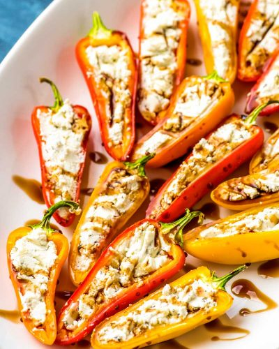 Goat Cheese Stuffed Mini Peppers! Tender sweet mini peppers filled with the pleasantly fresh (yet lightly tangy!) flavor of goat cheese and drizzled with balsamic reduction. | #ad #JoanofArcGoat @joanofarcbrie HomemadeHooplah.com