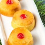 Mini Pineapple Upside Down Rum Cakes! Mini spongy yellow cakes topped with sweet pineapple and maraschino cherries that are generously brushed with Don Q Piña (pineapple rum). | #ad #Exceptional #DonQRum HomemadeHooplah.com