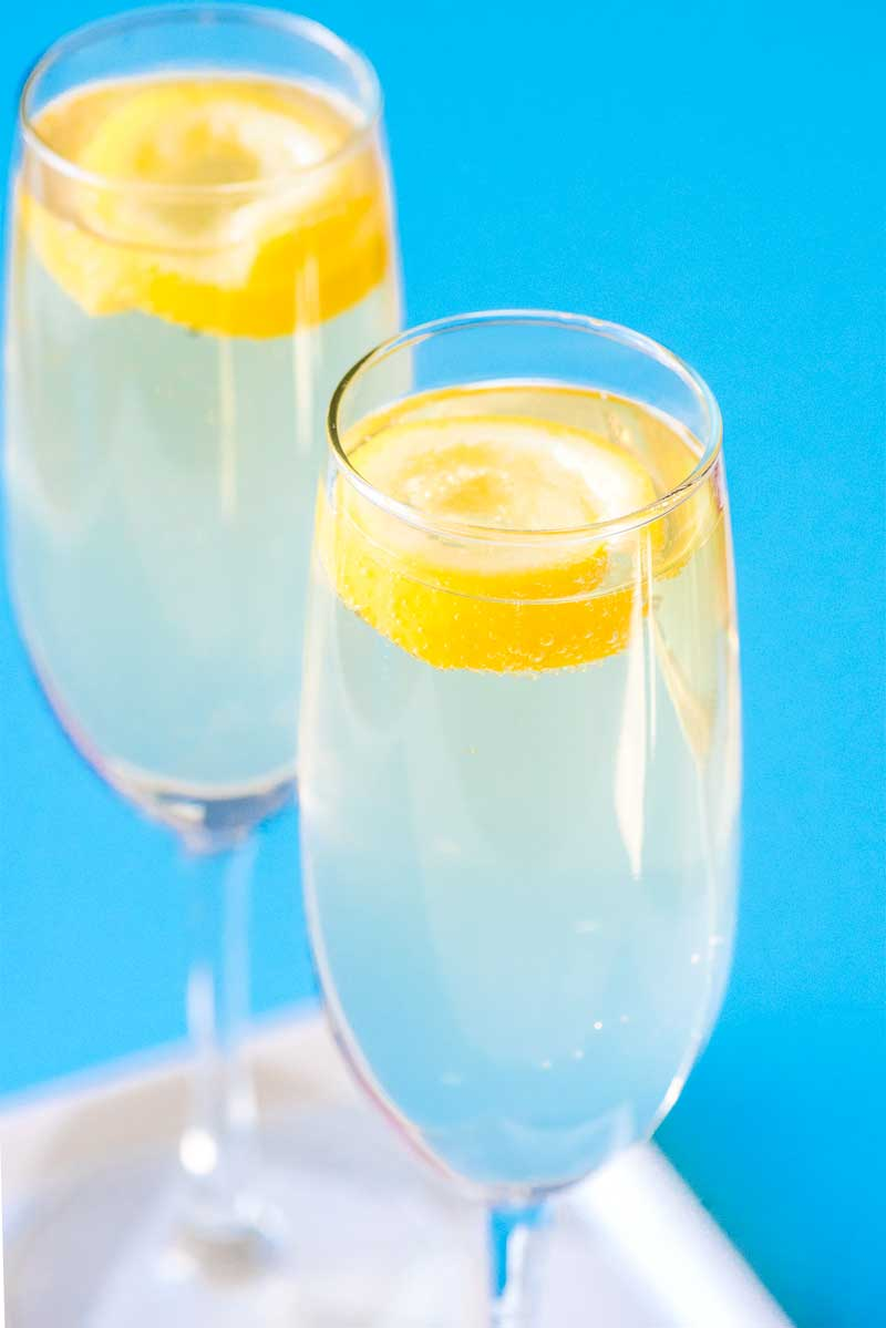 French 75! Also called the 75 Cocktail or simply 75, this effervescent drink flavored with lemon and dry champagne is both tart and refreshing. Plus, it's as easy to whip up as it is classy, making this pretty drink a great choice for any celebration. | HomemadeHooplah.com