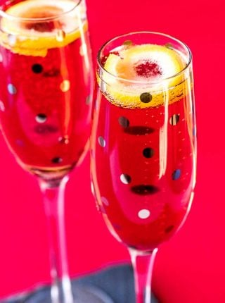 Kir Royale! This festive champagne cocktail combines the bite of dry champagne with the sweet, dark flavor of crème de cassis. A classic kir royal is the perfect dash of flavor and color for any party or celebration! | HomemadeHooplah.com
