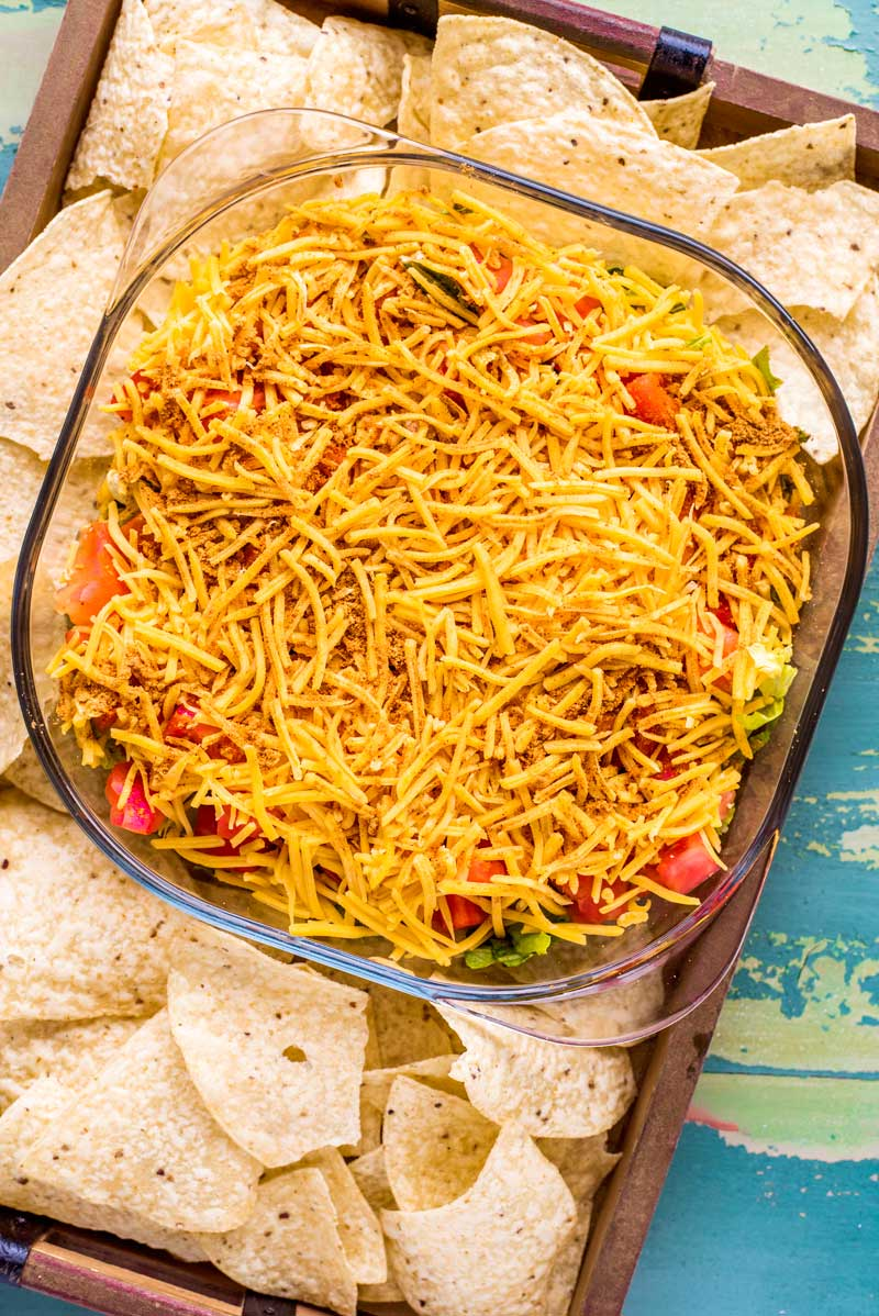 Taco Dip! This meatless layered taco dip packs a ton of seasoned flavor and is perfect for any holiday or game day party. Be sure to serve dip with plenty of tortilla chips and in a glass bowl so that guests can customize each scoop with the flavors they like! | HomemadeHooplah.com