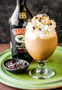 Irish Coffee! This fancy Irish coffee features all the best qualities of the traditional (such as dark brew coffee, Irish whiskey, and brown sugar) and takes it to the next level with a dash of Baileys, extra fluffy cream, chocolate shavings, and more brown sugar sprinkled on top. | HomemadeHooplah.com