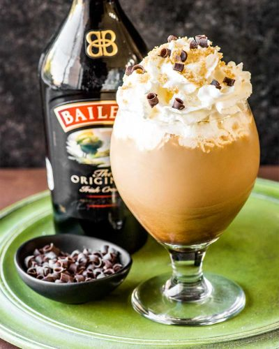 Irish Coffee! This fancy Irish coffee features all the best qualities of the traditional (such as dark brew coffee, Irish whiskey, and brown sugar) and takes it to the next level with a dash of Baileys, extra fluffy cream, chocolate shavings, and more brown sugar sprinkled on top.   HomemadeHooplah.com