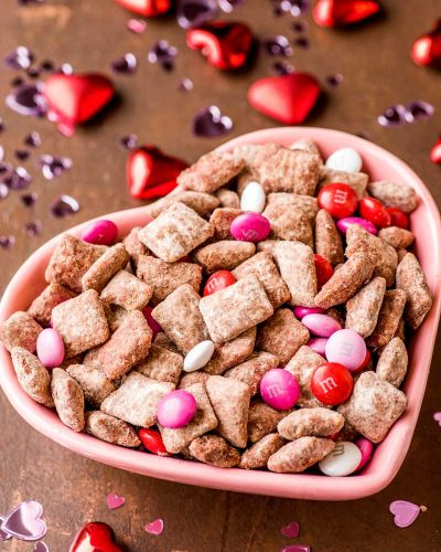 Red Velvet Puppy Chow! Classic puppy chow gets a classy makeover with decadent red velvet and festive M&M's. This red velvet puppy chow is perfect for every day snacking or a fun and festive homemade gift for any holiday or occasion. | HomemadeHooplah.com