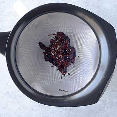 Blackberry Bourbon Lemonade Step 2 - Add blackberry mixture to a strainer.