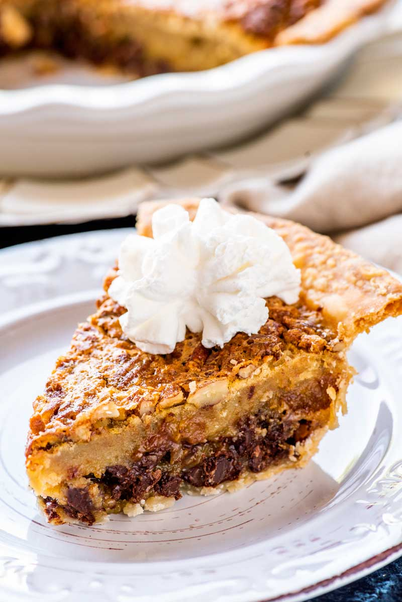 Kentucky Derby Pie! A total southern tradition, this Kentucky Derby pie is a creamy mix of chocolate chips and pecans. Whether you're watching the Derby or just need a crunchy chocolate fix, it's a must-make whenever the weather warms up! | HomemadeHooplah.com