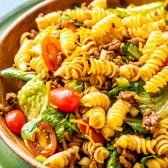 Taco Pasta Salad! Traditional taco pasta salad made with spiral pasta, ground beef, sweet tomatoes, veggies, plenty of cheese, and topped with sweet Catalina dressing. Classics are classic for a reason, and this fan-favorite recipe proves it!   HomemadeHooplah.com