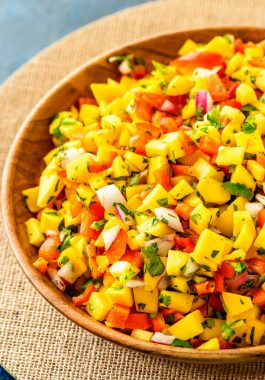 Mango Salsa! Classic and refreshing mango salsa made with mango, red peppers, onion, cilantro, lime juice, and an (optional!) dash of jalapeno peppers. Perfect as an easy party dip or a garnish with steak, chicken, or seafood. | HomemadeHooplah.com