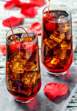 """Dracula's Kiss Cocktail! A vampire twist on a classic drink, this Dracula's Kiss is the spooky version of a cherry coke. Serve it with lots of ice and two """"puncture marks"""" (cherries). 