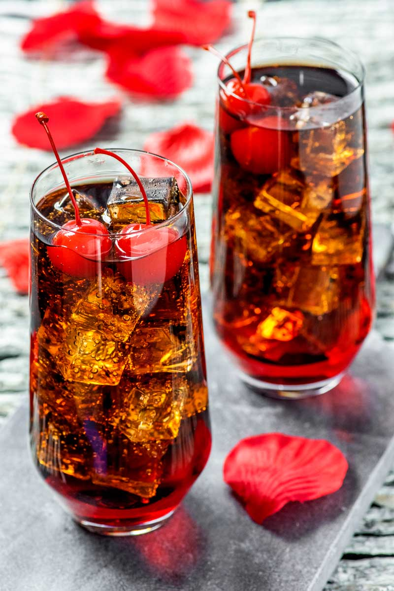 "Dracula's Kiss Cocktail! A vampire twist on a classic drink, this Dracula's Kiss is the spooky version of a cherry coke. Serve it with lots of ice and two ""puncture marks"" (cherries). 