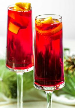Poinsettia Cocktail! This poinsettia cocktail has the refreshingly tart taste of cranberry juice mixed with orange liqueur then topped with bubbling champagne and an orange twist. | HomemadeHooplah.com