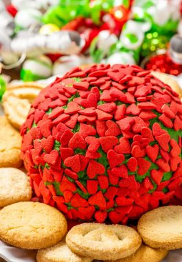 Grinch Cheese Ball! Perfect for the holidays, this Grinch-themed cheese ball has a green hue and is covered in tiny heart-shaped sprinkles. Plus, it can be made different flavors! | HomemadeHooplah.com