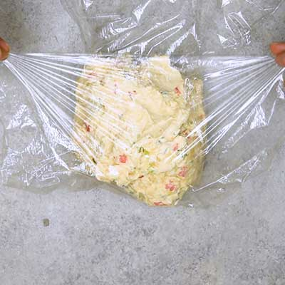 Pineapple Cheese Ball Step 3 - Pull plastic wrap around cream cheese mixture, forming a ball.