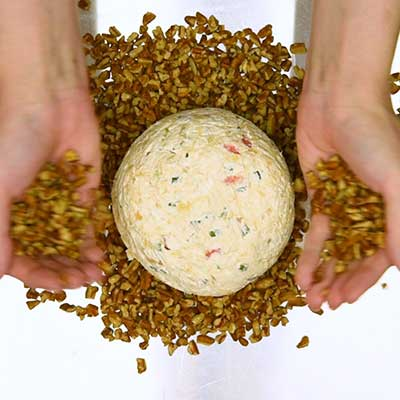 Pineapple Cheese Ball Step 5 - Press pecans into the surface of the cheese ball.
