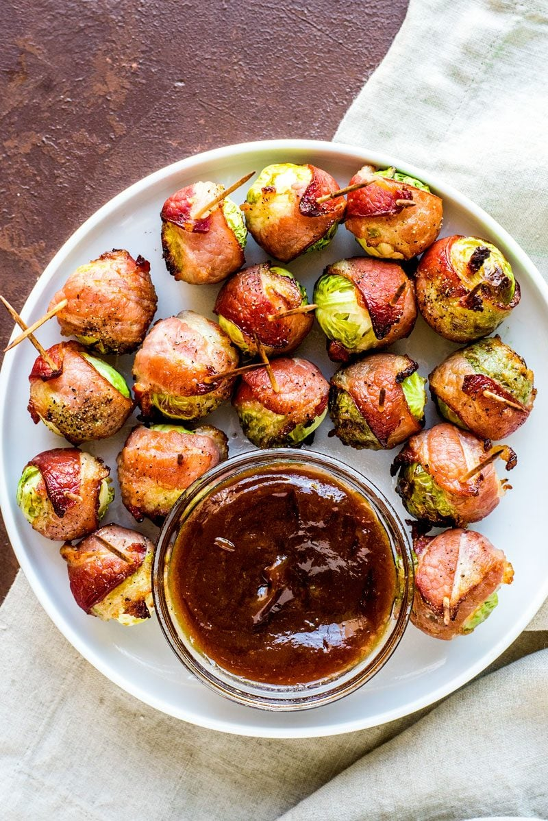 Bacon Wrapped Brussels Sprouts! When it comes to creative appetizers, these bacon wrapped Brussels sprouts with maple syrup are sure to steal the show. Get the instant appeal of bacon, the savory greens of the sprout, and a dash of maple syrup all in one easy finger food. | HomemadeHooplah.com
